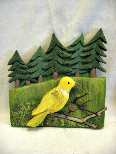 Charlie Poirier. Cheticamp. An applied carving. A bird in the forest.