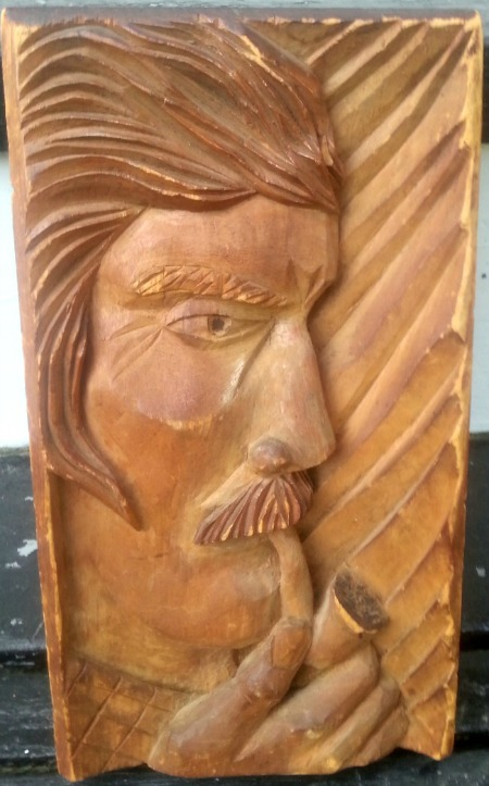 J. E. Guindon. Montreal, Quebec. Relief carving of a man smoking a pipe.